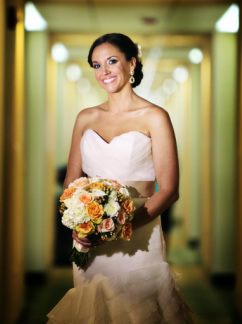 Bride holding a custom flower bouquet of white and orange roses